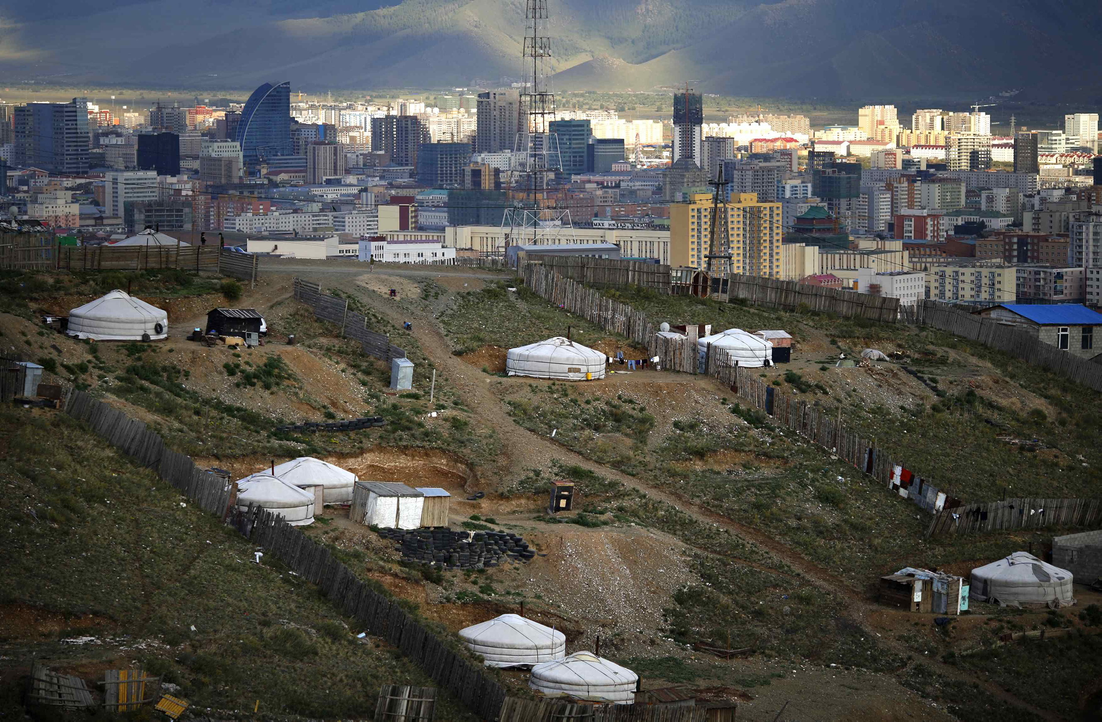 Gers, traditional Mongolian tents, are seen on a hill in an area known as a ger district in Ulan Bator June 26, 2013. Approximately 60 percent of the population of Ulan Bator live in settlements known as ger districts and in many cases residents have limited access to basic services such as water and sanitation. According to a 2010 National Population Center census, every year between thirty and forty thousand people migrate from the countryside to the capital Ulan Bator. Ger districts in the city have been expanding rapidly in recent years. Mongolia is the world's least densely populated country, with 2.8 million people spread across an area around three times the size of France. (Photo by Carlos Barria/Reuters)