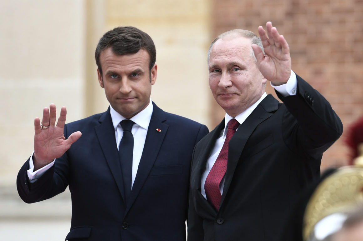 Russian President Vladimir Putin (R) and French President Emmanuel Macron (L) wave upon their arrival at the Versailles Palace, near Paris, on May 29, 2017, ahead of their meeting. French President Emmanuel Macron hosts Russian counterpart Vladimir Putin in their first meeting since he came to office with differences on Ukraine and Syria clearly visible. / AFP PHOTO / STEPHANE DE SAKUTIN        (Photo credit should read STEPHANE DE SAKUTIN/AFP/Getty Images)